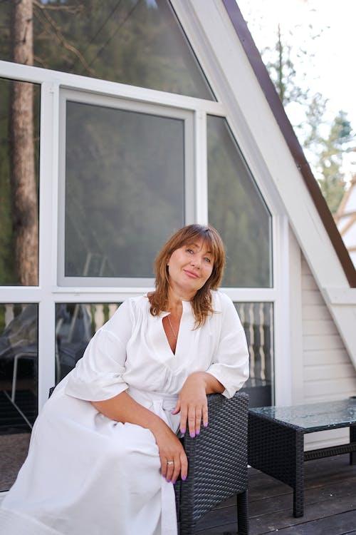 Woman in white dress sitting in armchair on veranda