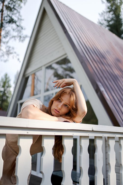 Thoughtful woman dreaming on balcony of rural house