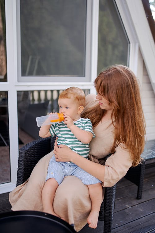 Female with little boy drinking from bottle while sitting in armchair on house terrace