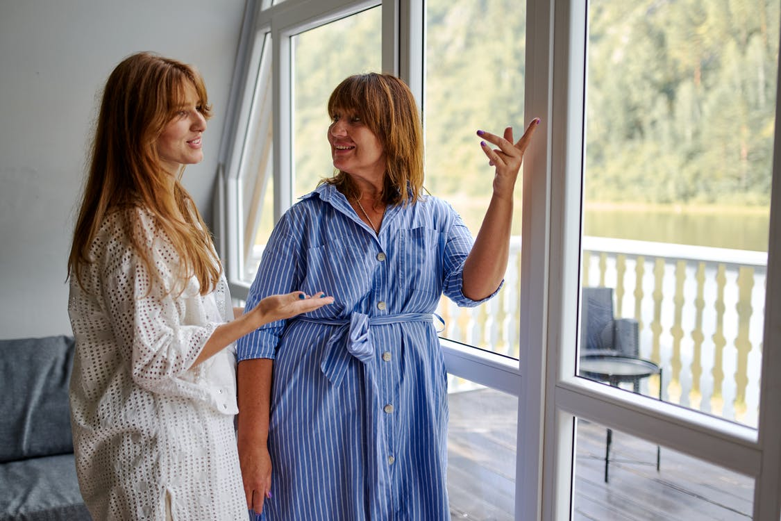Mother and daughter discussing weather outise house