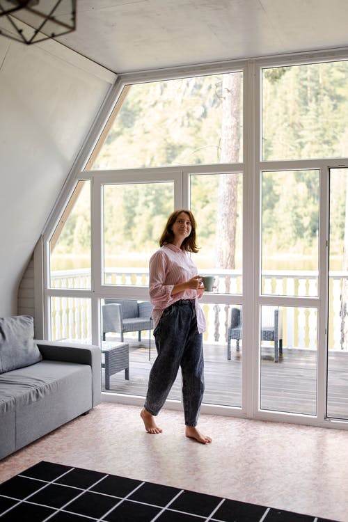 Female in home clothes looking away walking around living room with cup of tea