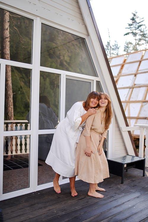 Cheerful women hugging on open terrace