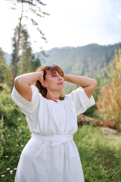 Serene woman in white dress touching head gently in nature