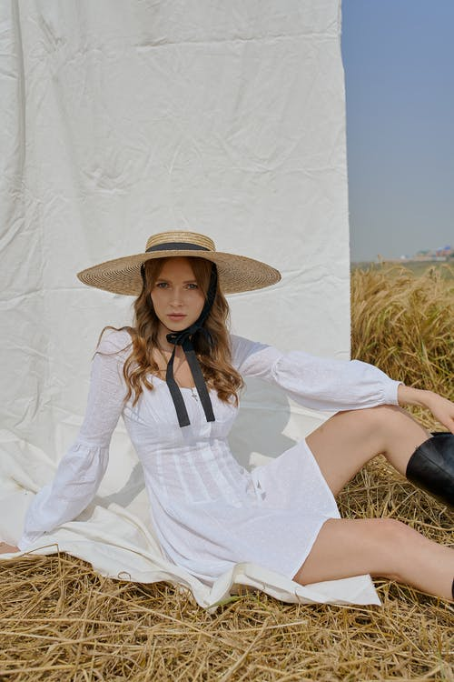 Emotionless woman in trendy outfit sitting on straw in field