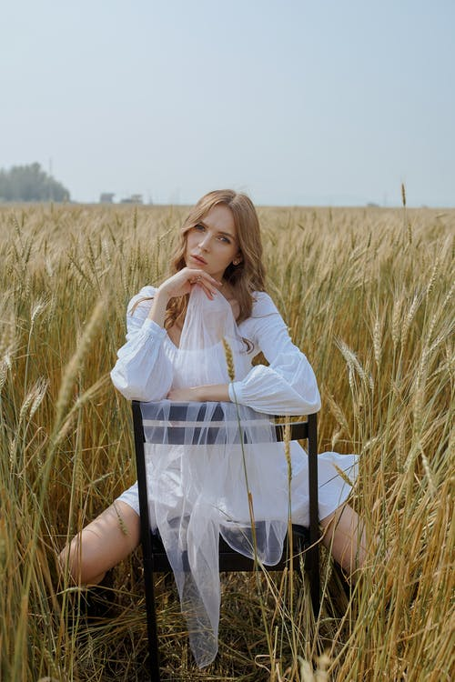 Full body calm young female model in white dress sitting backwards on wooden chair with white veil in hand on spacious agricultural field and looking at camera