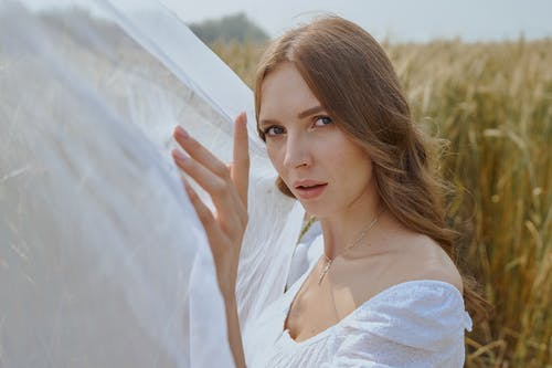 Tender young woman standing on field near waving white veil
