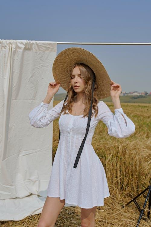 Stilvolle Frau, Die Auf Feld Steht Und Hutkrempen Berührt