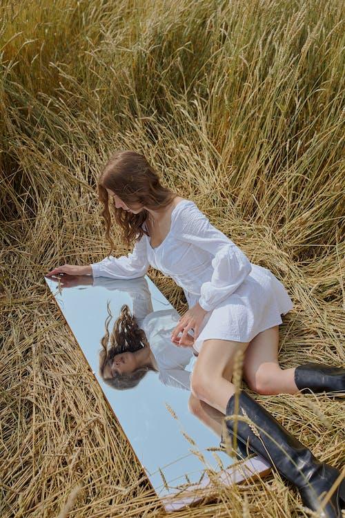 Stilvolle Frau, Die Auf Feld Liegt Und Im Käferspiegel Schaut