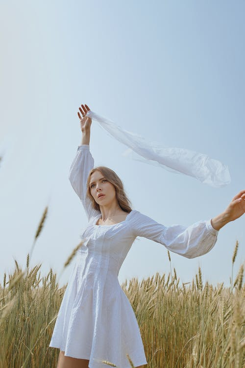 Serene young female wearing white mini dress standing with white waving scarf in raised hand on agricultural field and looking away