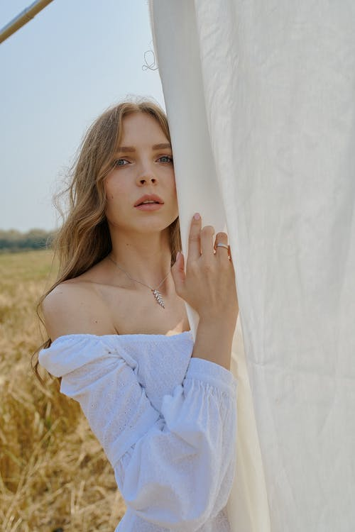 Serene young female wearing white dress with bare shoulders standing near hanging white sheet on sunny summer field and looking at camera