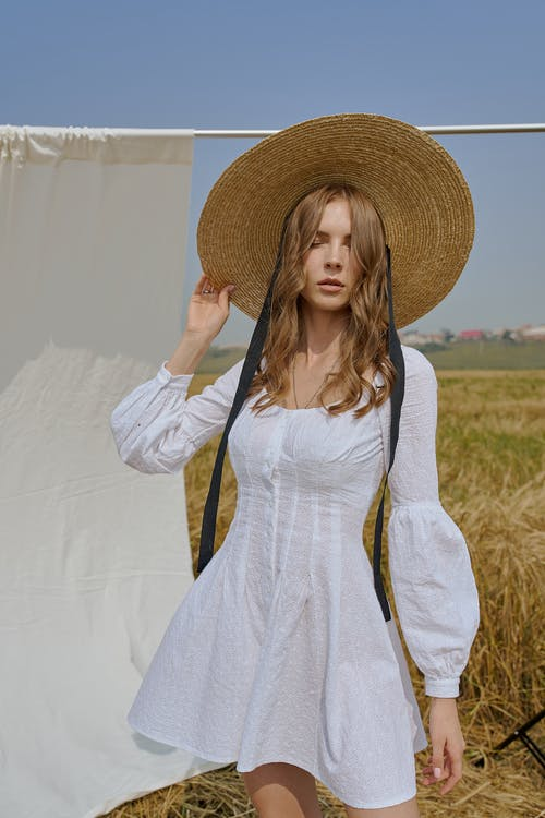 Attractive woman in white summer dress standing on field