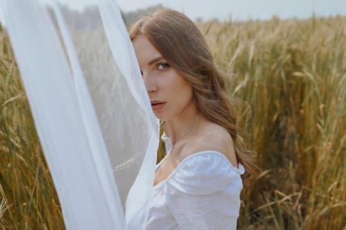 Beautiful woman standing on grassy meadow near waving veil