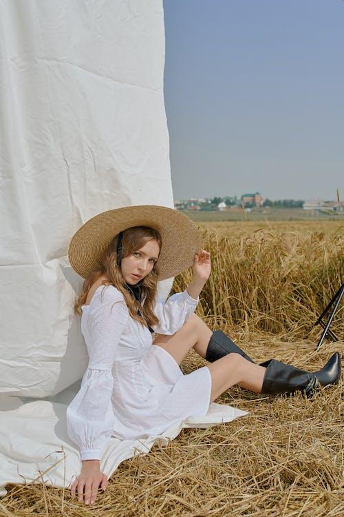 Trendige Frau Im Weißen Sommerkleid, Das Auf Landwirtschaftlichem Feld Sitzt