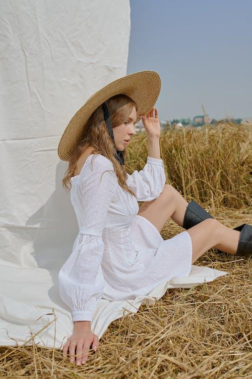 Stilvolle Frau Im Weißen Kleid, Das Auf Heu Sitzt