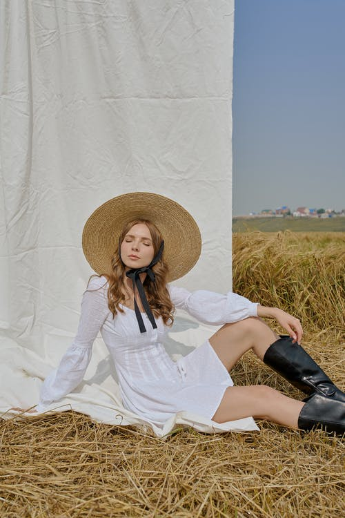 Relaxed stylish woman resting on straw in agricultural field