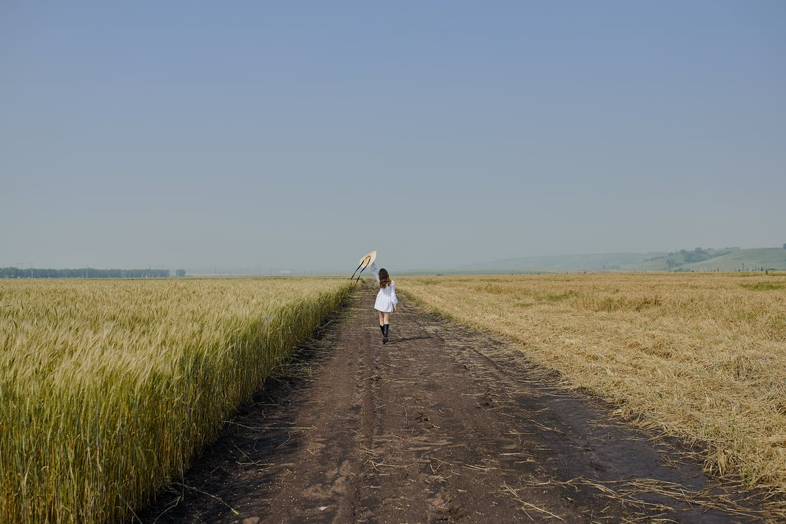 Full length of unrecognizable female in stylish white dress raising hand with straw hat and walking on road in field with dry grass in countryside under cloudless clue sky