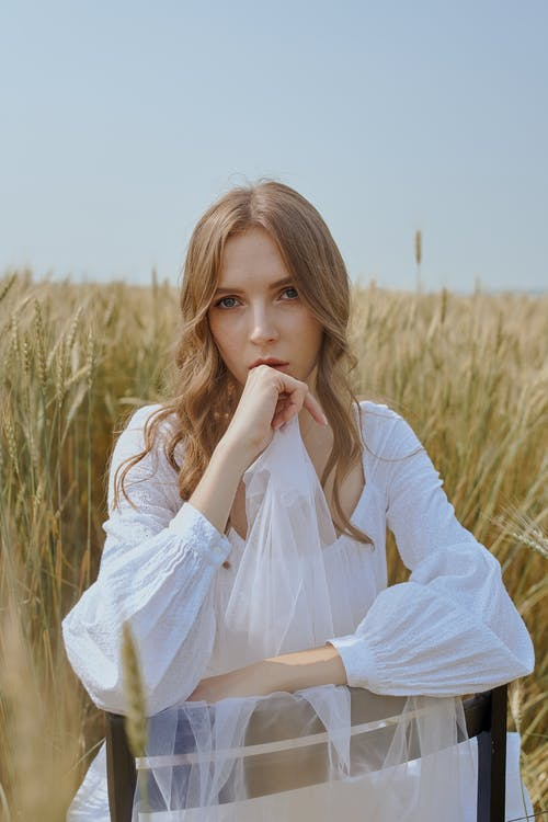 Pensive female with long wavy hair in stylish outfit touching chin and sitting on chair in field of wheat located in countryside in sunny day