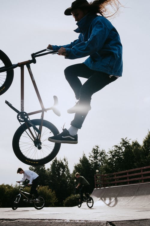Man in Blue Jacket Riding on Black Bmx Bike