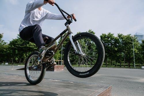 Man in White Long Sleeve Shirt Riding on Black Bmx Bike