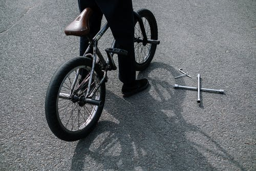 Person in Black Pants Riding Black Bicycle on Gray Concrete Road