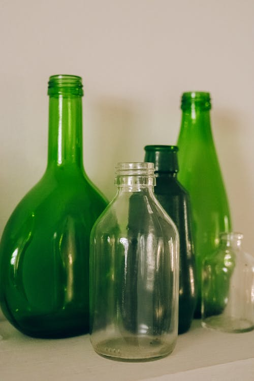 Collection of shiny green and transparent glass bottles on white table near wall