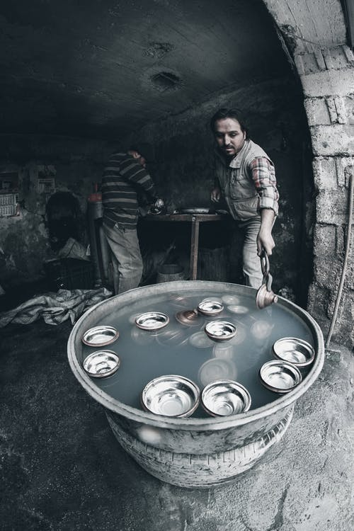 From above of ethnic male worker cooling metal bowls in container with water using tongs near unrecognizable partner