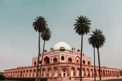 Exterior of famous ancient building located in Delhi in India named Humayun Tomb in summer day under cloudless sky near tall exotic trees