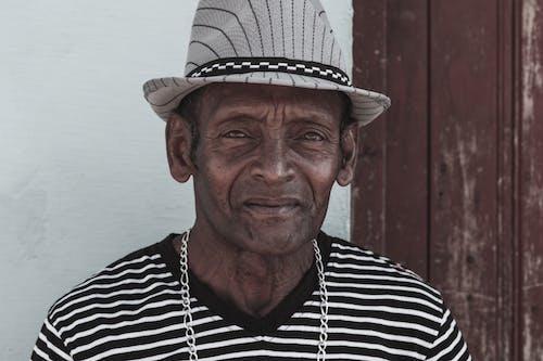 Senior ethnic man in striped hat near wall