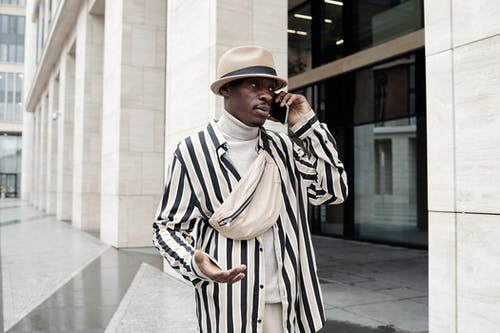 Man in White and Black Stripe Long Sleeve Shirt Wearing Brown Hat Standing Near White Concrete