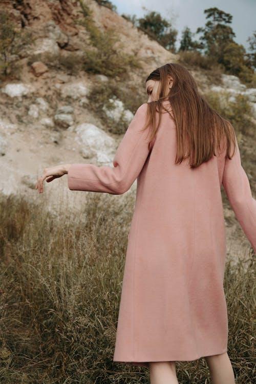 Woman in Pink Sleeveless Dress Standing on Brown Grass Field