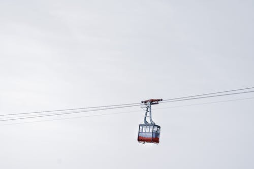 Cable car riding on ropeway in wild nature against gray cloudy sky at daytime