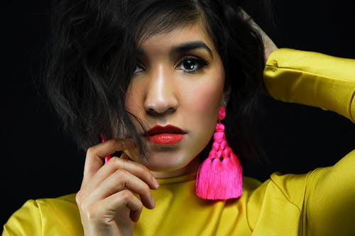 Crop serious female with brown eyes and hairstyle in bright yellow turtleneck touching head and looking at camera against black background