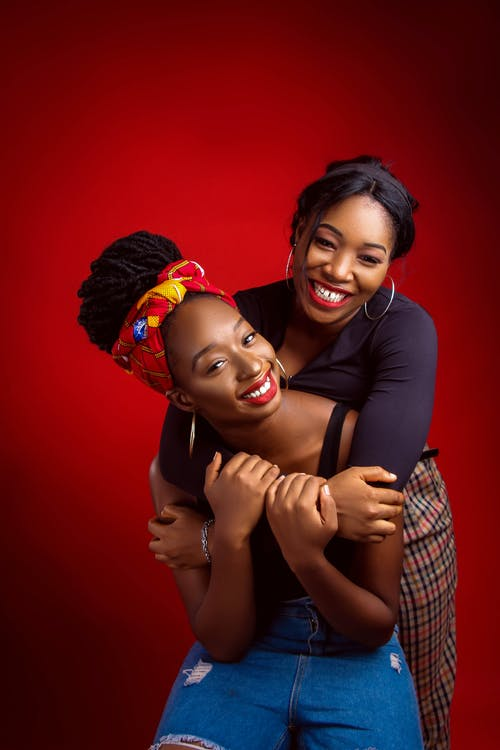 Happy African American women in casual clothes hugging and looking at camera against bright red background