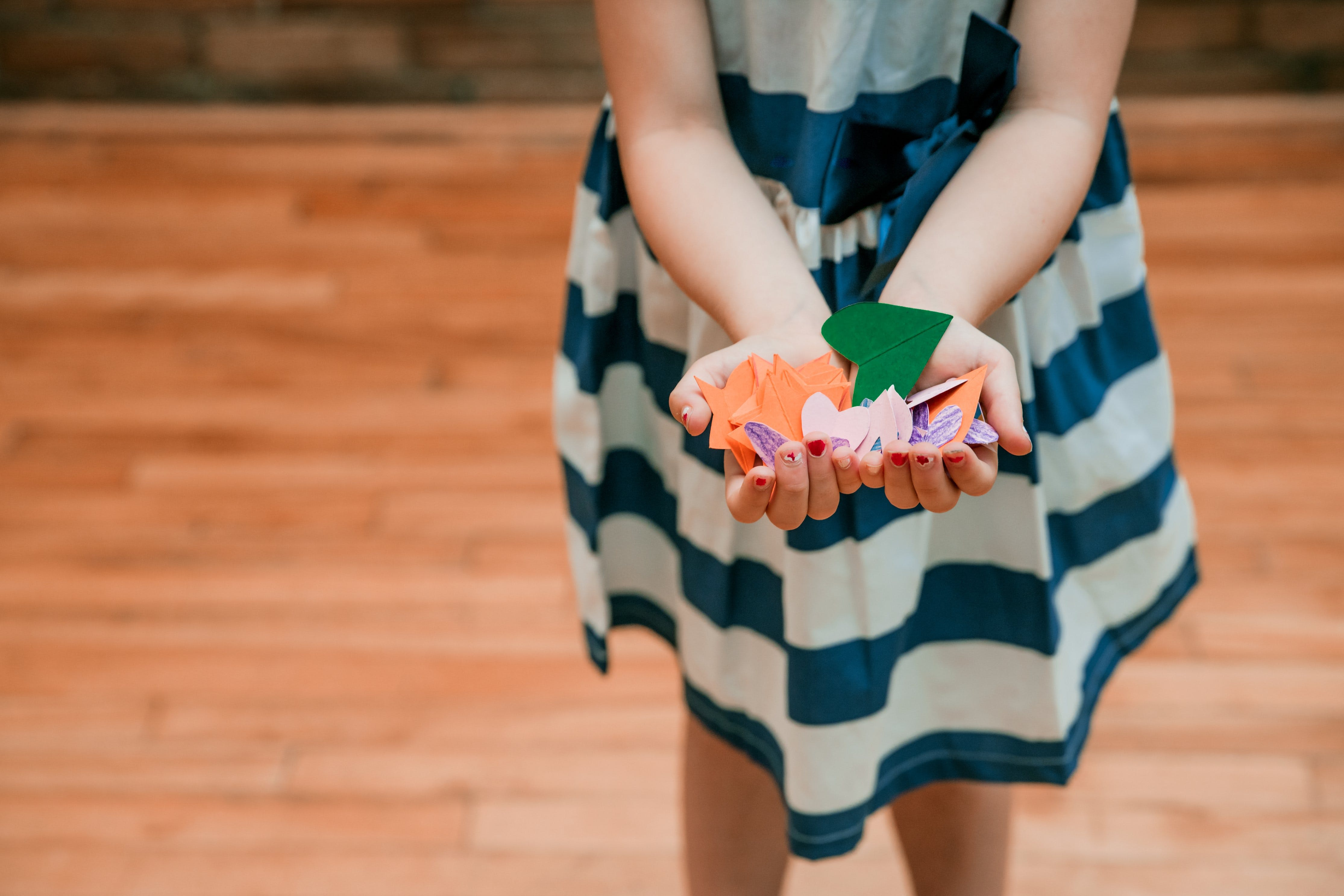 Girl Holding Orange and Green Cut Papers