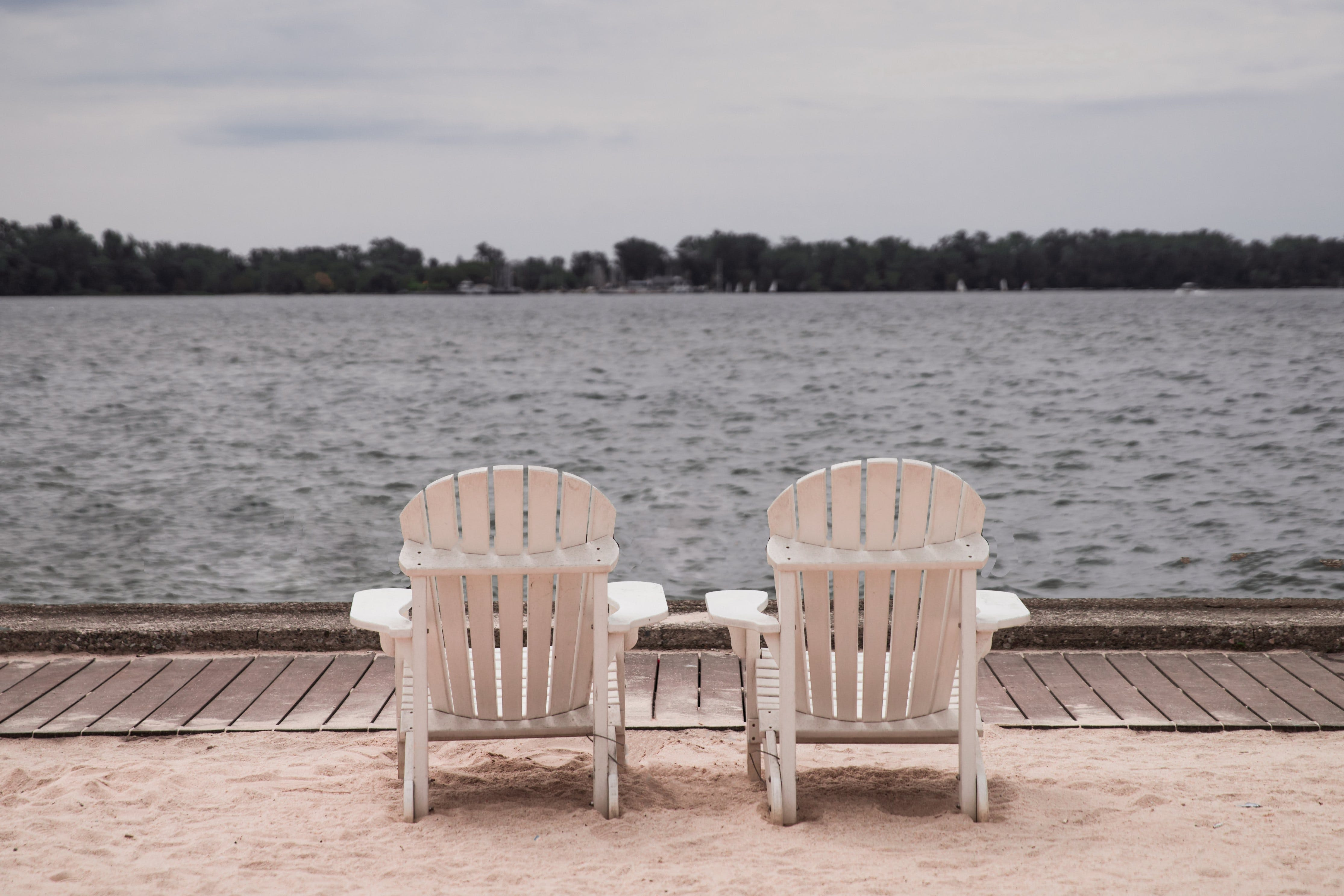 Two White Lounge Chairs Beside Body of Water