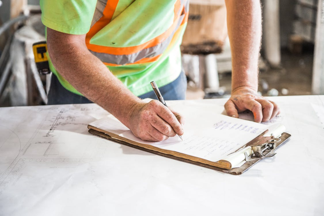Construction worker Writing on a clipboard on Top of Table