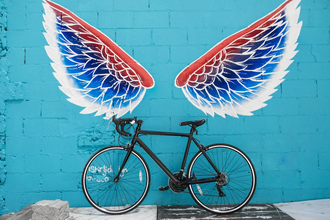 Black Road Bike Leaning on Red-blue-and-white Wing Graffiti Wall