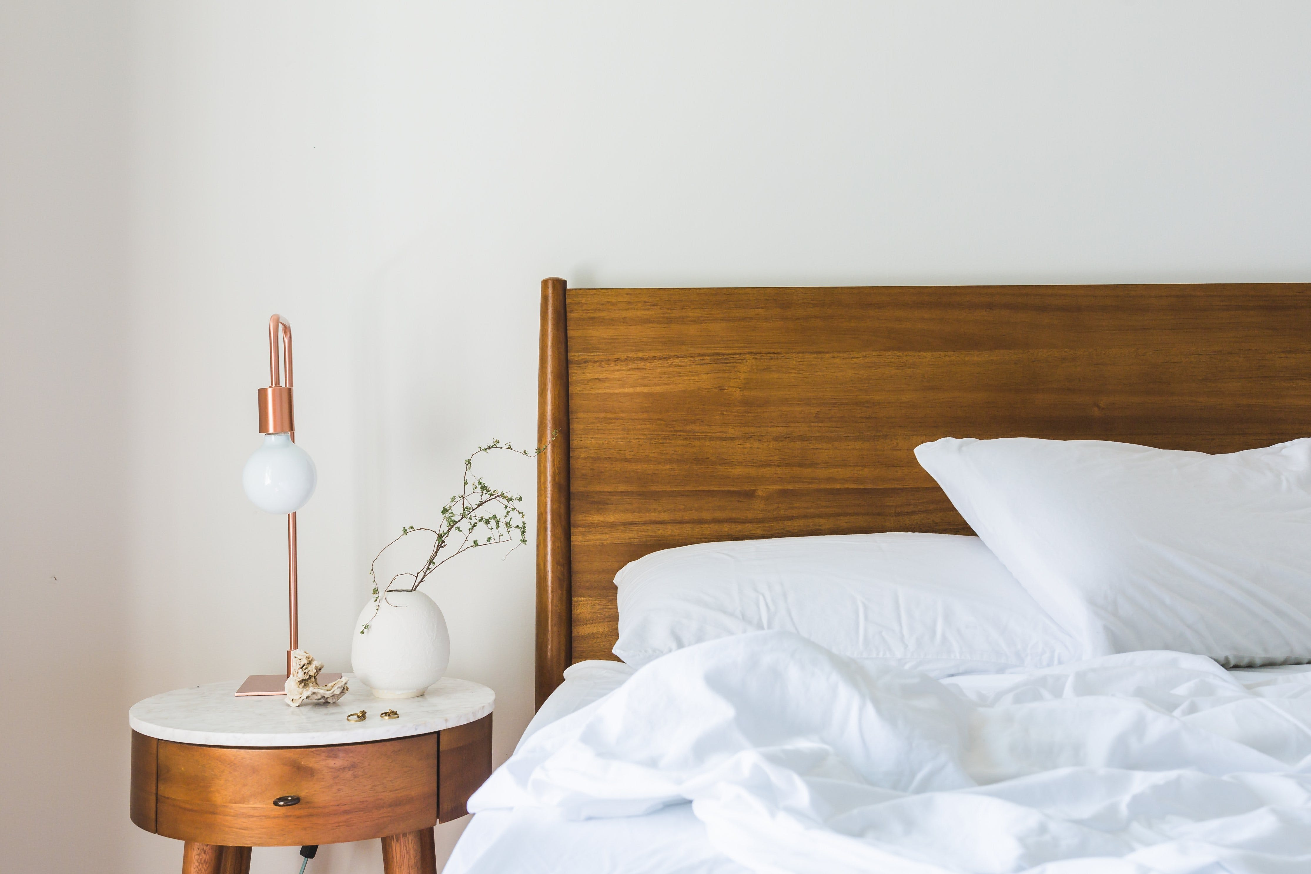 White Bedspread Beside Nightstand With White and Copper Table Lamp