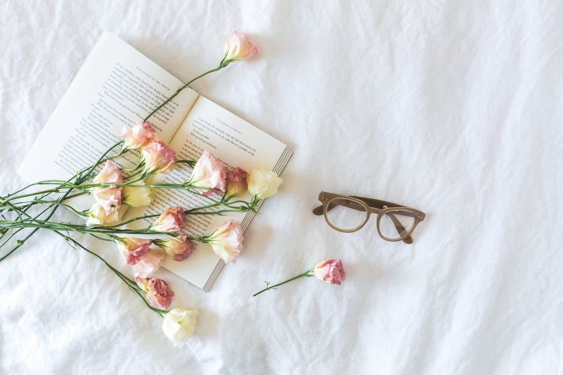 White and Pink Flowerson a book beside Eyeglasses