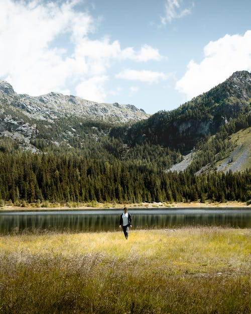 Man in Black Jacket and Black Pants Walking on Green Grass Field Near Lake and Mountains