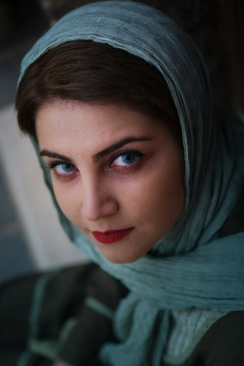 Pensive young female with dark hair and blue eyes in headscarf looking at camera