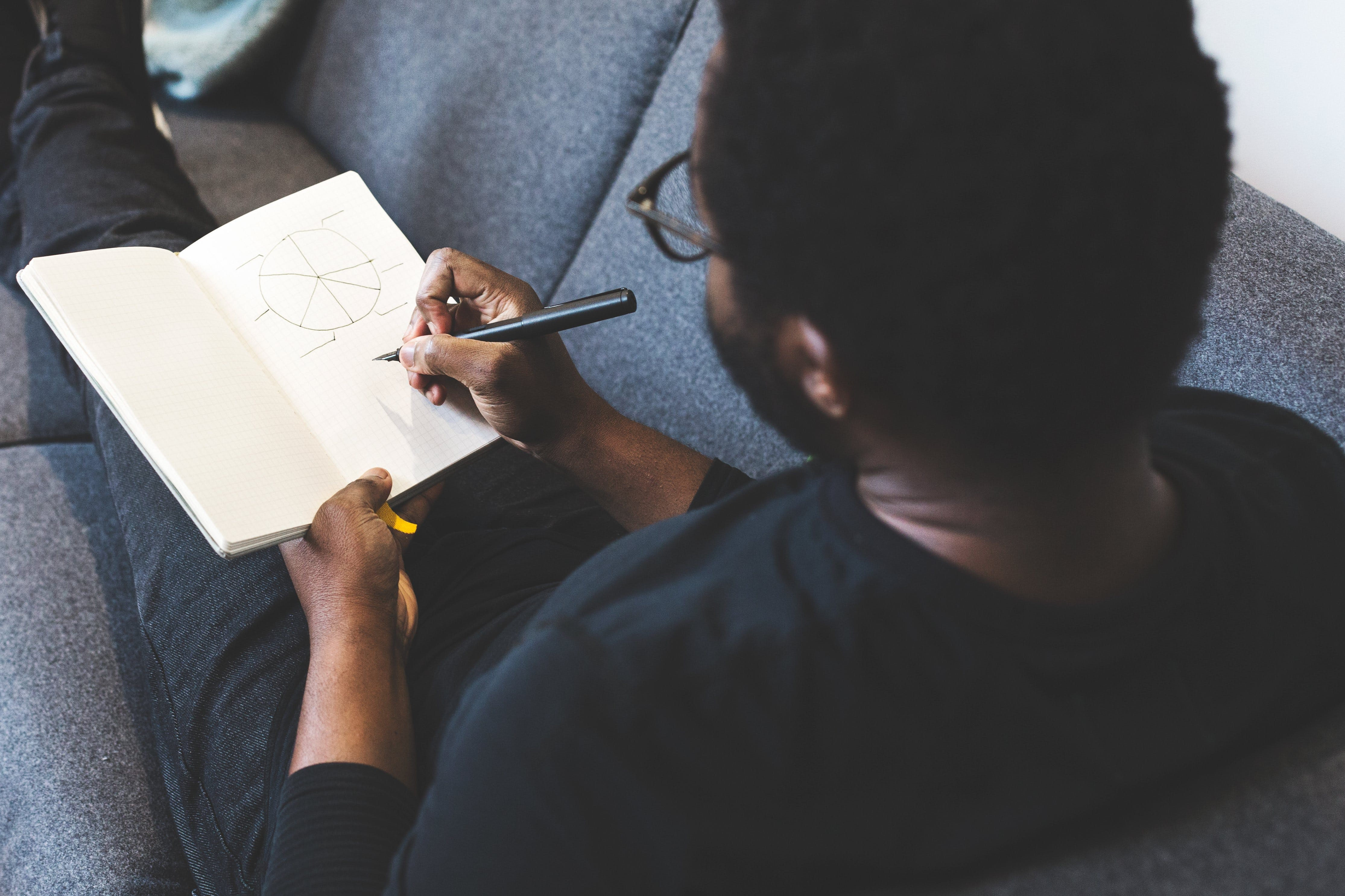 Man Sitting on Gray Couch Writing on White Book