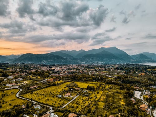 Picturesque landscape of peaceful countryside with typical residential houses and green trees located near mountains under cloudy sunset sky