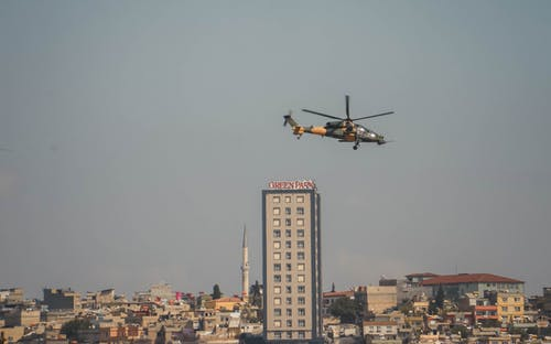 Black and Yellow Helicopter Flying over City Buildings