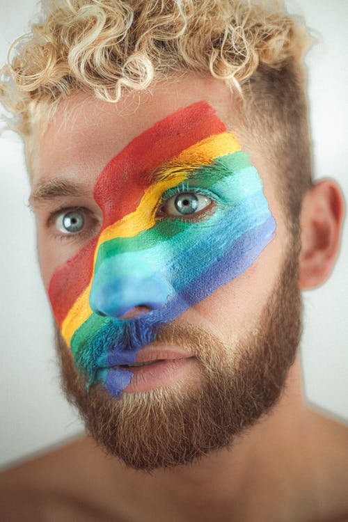 Crop handsome calm male with bright LGBT flag painted across face standing in light studio and looking away