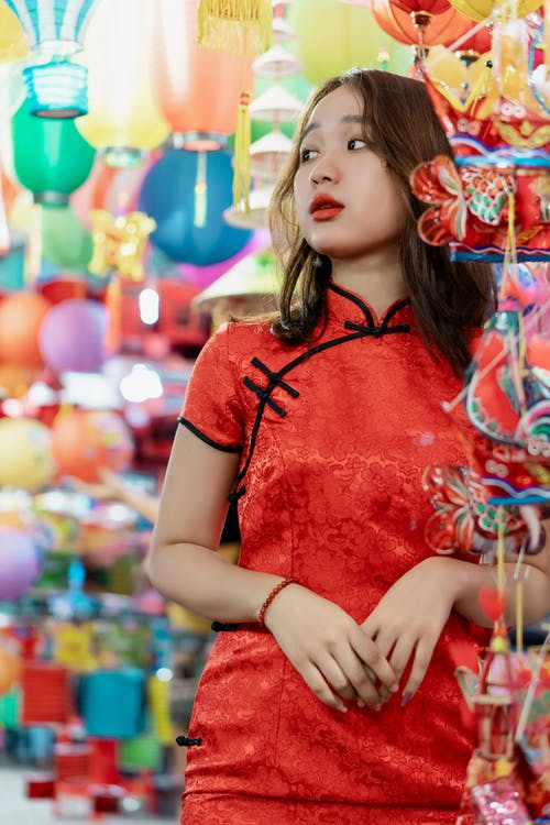 Contemplative ethnic female teenager in elegant red dress looking away among  assorted bright lanterns