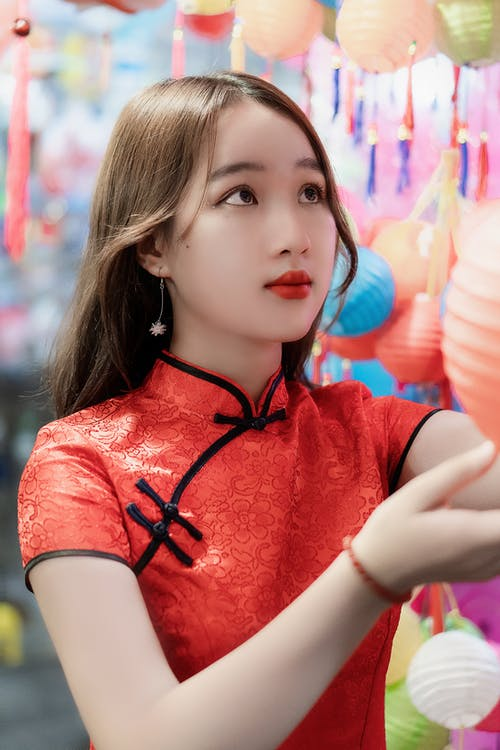 Dreamy Asian female teen with makeup in trendy wear touching colorful lantern while looking up