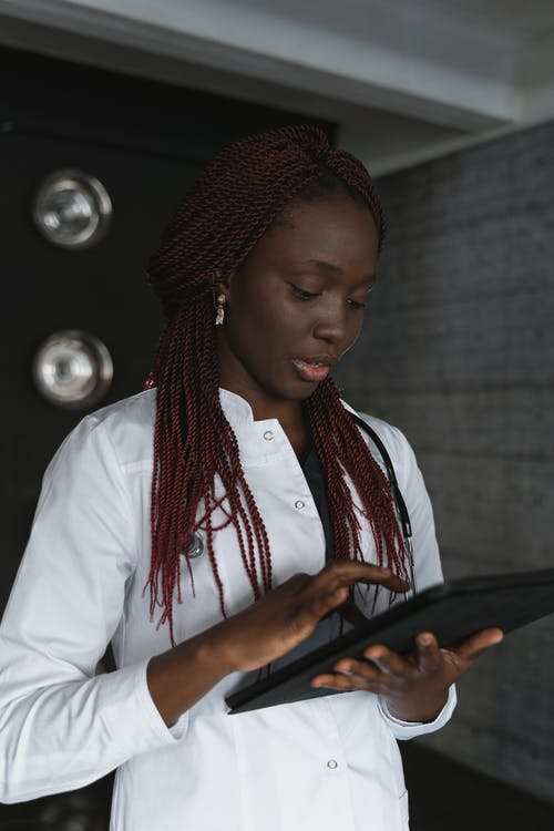 Woman in White Long Sleeve Shirt Holding Black Tablet Computer