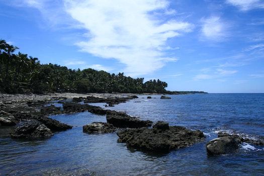 Large Rocks on Seashore Under White Cloudy Sky during Daytime
