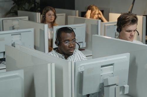 Man in Black Framed Eyeglasses Sitting Beside Woman in White Shirt